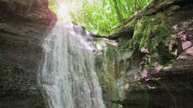 Forest waterfall falling on rocky cliff in sunny summer day with sudden rain — Stock Video