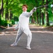 Young beautiful rapier fencer woman staying in park alley ready — Stock Photo #68882439