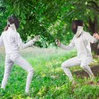 Two rapier fencer women fighting over beautiful nature park back — Stock Photo #68882503