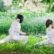 Two rapier fencer women fighting over beautiful nature park back — Stock Photo #68882505