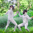 Two rapier fencer women fighting over beautiful nature park back — Stock Photo #68882509