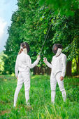 Two fencers women staying in park with crossed rapiers  — Stock Photo