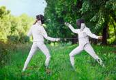 Two rapier fencer women fighting over beautiful nature backgroun — Stock Photo