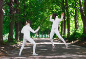 Two rapier fencer women fighting over park alley, attacking each — Stock Photo