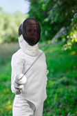 Fencer woman staying over beautiful nature background with rapie — Stock Photo