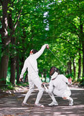 Two rapier fencers women fencing on park path — Stock Photo