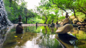 Meditate spiritual landscape of green forest with calm pond water and stone balance rocks — Stock Photo