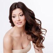 Vacker kvinna med lockigt brunt hår — Stockfoto