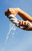 Hands squeeze wet fabric against blue sky. — Stock Photo