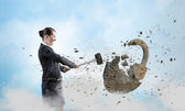 Businesswoman crashing stone lock — Stock Photo