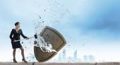 Businesswoman crashing stone shield — Stock Photo
