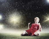 Football player standing on knees — Stock Photo