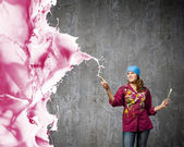 Painter with brush and colorful splashes — Stock Photo