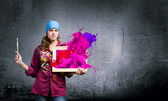 Painter holding frame with colorful splashes — Stock Photo