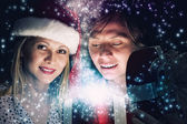 Man and woman opening Christmas gifts — Stock Photo