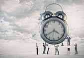 Clock and many businesspeople around — Foto Stock