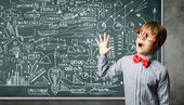 Genius boy near blackboard with formulas — Stock Photo