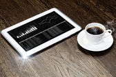 Tablet pc, cup of coffee and notepad — Stock Photo
