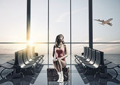 Traveler at airport sitting on suitcase — Stock Photo
