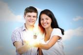 Couple holding electric bulb — Stock Photo