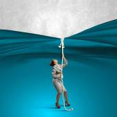 Businesswoman pulling curtain with rope — Stock Photo