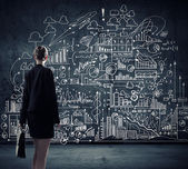 Businesswoman looking at business sketches — Stockfoto
