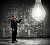 Businessman switching on light bulb — Stock Photo