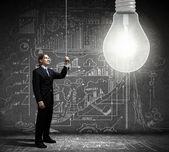 Businessman switching on light bulb — Stock Photo