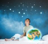 Boy sitting in bed and holding Earth planet — Stock fotografie