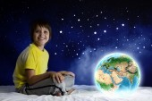Boy sitting in bed holding Earth planet — Стоковое фото