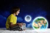 Pojken sitter i sängen håller jorden planet — Stockfoto