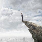 Businessman on edge of rock — Stock Photo