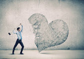 Businessman breaking stone heart — Stock Photo