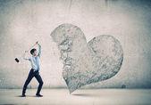 Businessman breaking stone heart — Stock Photo