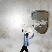 Businessman crashing shield with hammer — Stock Photo