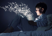 Boy using tablet pc in bed — Stock Photo