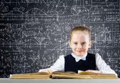 Schoolgirl at lesson with book — Stock Photo