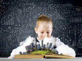 Schoolgirl looking at book — 图库照片
