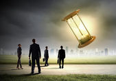 Business people looking at sandglass — Stock Photo