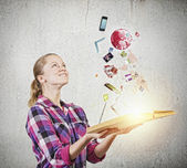 Woman holding book with flying icons — Stock Photo