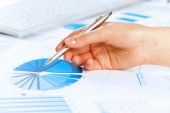 Hand holding pen and pointing at graphs — Stock Photo