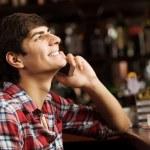 Man talking on phone at bar — Stock Photo