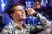 Man talking on phone at bar — Stock Photo