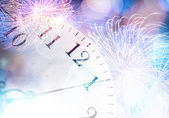 Clock with bokeh lights and firework — Stock Photo