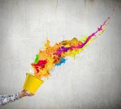 Hand splashing colorful paint — Stock Photo