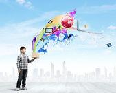 Boy splashing colorful paint — Stock Photo