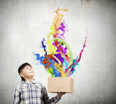 Boy splashing colorful paint — Stock Photo