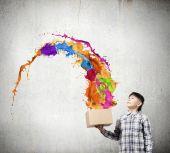Boy splashing colorful paint — Stockfoto