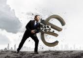 Businessman breaking euro sign — Stock Photo