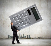 Businessman carrying big calculator — Stock Photo